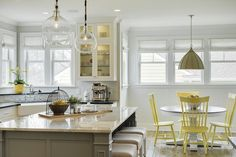 Yellow and gray kitchen features a pair of glass globe pendants hanging over a gray kitchen island topped with grey and white quartzite lined with gray linen backless counter stools.
