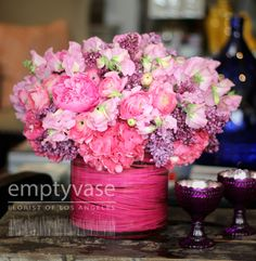 """Empty Vase Florist of Los Angeles  Palisades Pink  This brilliant bouquet is arranged with pink hydrangeas, sweetpea, lilacs, peonies, ranunculas and hyacinth in a glass vase with spiraling pink middolina. The vase measures 8""""h x 8""""w and the arrangement is approx. 16"""" tall."""