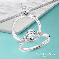 Diamond wings take flight on both sides of the center stone, creating the perfect ring if you want to sweep her off her feet. #Valina #diamonds #bridaltrends #perfectwedding #wedding2021 #2021weddings #ringbling #bridetobe #heputaringonit #engagementringideas #diamondrings #bridalcouture #engagementrings #weddingdreams #whitegold #straightengagementring #whitegoldengagementring #statementring #statementengagementring #bridalset #vintageengagementring #vintagejewelry