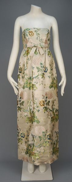 RICHARD TAM SILK BROCADE EVENING DRESS and JACKET, c. 1964 Champagne silk brocaded in an 18th C inspired polychrome floral, strapless gown having boned Empire bodice with attached self belt and center bow, cropped princess line jacket with back self buttons and three quarter sleeve, silk lining.