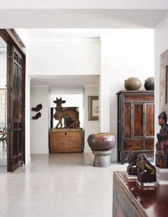 A beautiful home in south Africa - love the wooden nandi vahanam from south india, and the dark wood chinese doors