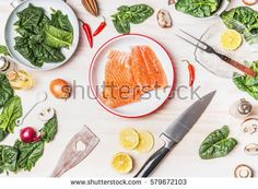 Top view of kitchen table with salmon , spinach leaves , kitchen knife and pan, cooking preparation on white wooden background , top view