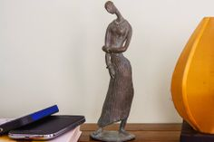 A simple figurine of a lady - consisting of lucid lines. A bronze statuette to beautify your living room  Product id - SP01 Product Description - Stauette of a Lady in Lost wax, Bronze, Size - 9.5in * 3in * 2.5in Artist - Subrata Paul  For enquiries, call or whatsapp to +91 9007798937.