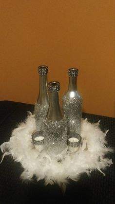 Picture this centerpiece used for a Masquerade party, birthday party, or even an anniversary party. This centerpiece includes: 3 glittered wine bottles and 3 candles The size of this centerpiece is 12 inches (1ft) tall by 9 inches wide. Bulk orders may take longer to ship