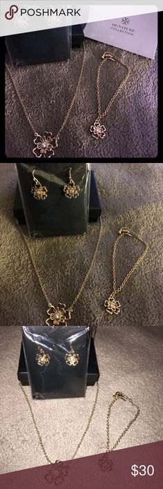 AVON 3 piece in bloom set - gold tone New in box. Received as gift. Beautiful 3 piece set- earrings, bracelet, necklace .. gold tone with diamond in center of bloom petals Avon Jewelry Necklaces