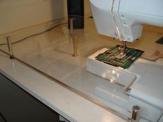 home made plexiglass sewing machine extension table-can use dowels and leveling feet