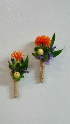Adorable jute wrapped jr. boutonnieres of orange safflower, purple limonium and ivory hypericum from Seasonal Celebrations.
