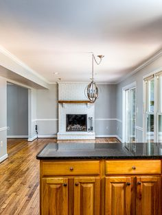This family room has great sight lines into the kitchen! With medium tone hardwood flooring, modern light fixture, white brick fireplace and wood mantle, and plenty of natural light. Listed for $849,900 in Vienna by The Casey Samson Team, a Wall Street Journal Top Team in Northern Virginia.