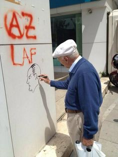 """A man draws a picture of M. K. Ataturk on the wall 