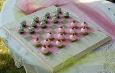 Polymer clay cupcakes on a distressed checker board.