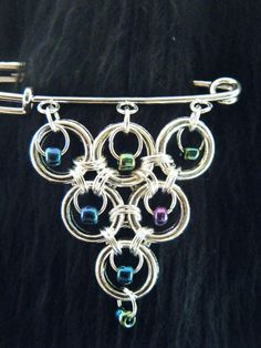 Use jump rings and a Kilt pin for a great jewelry piece!
