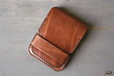 This handmade leather wallet is crafted using rich full-grain harness or bridle leather. The slim minimalist design has an inner card holder, and a narrow sleeve for your bills. Its a very thin wallet with just a few cards, but it can also stretch to carry 10 plus. It closes securely