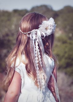Peinados para primera comunión con el pelo suelto y una corona de cintas con una flor de tela