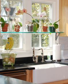 Floating glass shelving installed in front of a kitchen window is a great way to display artful planters! www.franksglass.com