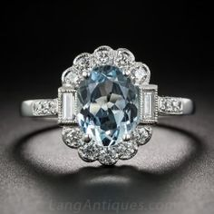 Vintage Style Aquamarine and Diamond Ring - Crafted in gleaming 18K white gold, in timeless vintage style, this cheerful bauble glistens and glows with a bright, light pastel blue, oval aquamarine. The gemstone fills a sparkling white diamond halo punctuated by a pair of baguette diamonds, leading to a currently size 7 1/2 ring shank, enlivened with a tiny trio of diamonds glinting on the shoulders.