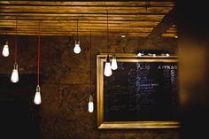 turned on pendant bulb lot beside wall decor Rustic Restaurant Lampe Globe, Lampe 3d, Home Lighting, Lighting Design, Track Lighting, Nordic By Nature, Arc Lamp, Rustic Restaurant, Oil Lamps