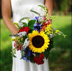 Focused on a sunflower, and surrounded by Dianthus, Delphinium, Snapdragons, Veronica and Solid Aster.