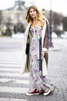 A shearling coat is worn over a floral cami dress, paired with high top Converse sneakers