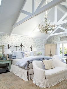 Via Better Homes & Gardens - blue bedroom. This cottage bedroom has all the elements to make it a classic, from the painted white woodwork and beaded-board wainscoting to the crisp-white slipcovers and ruffled bedskirt. Blue-and-white bedding and pretty floral wallpaper complete the picture. The ornate chandelier is the icing on the cake for this romantic bedroom.
