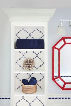 Boy's bathroom with blue walls, red faux bamboo mirror, white built-in cabinet lined with Caitlin Wilson Textiles Navy Souk Trellis Fabric, Visual Comfort Lighting Boston Square 3 Light Sconce and blue towels. New Blue, Blue And White, Blue Painted Walls, Blue Walls, Wall Paint Colors, Faux Bamboo, White Rooms, Decorating Your Home, Decorating Ideas