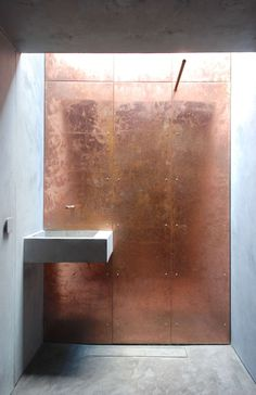 Brutalist #bathroom wall cladded in a patinad #copper