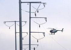 A helicopter starts the process of stringing a high-voltage transmission line