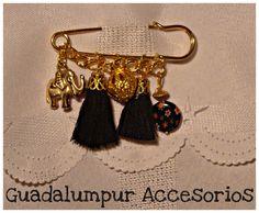 FLORES Y ELEFANTES  Alfileron dorado con dije elefante, borlas negras y piedra negra con flores.  • $25  facebook.com/guadalumpur.accesorios  guadalumpur@gmail.com