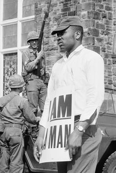 """National Guardsmen look on as African-American protesters begin a march to downtown Memphis wearing placards reading, """"I AM A MAN."""" It was the third consecutive march held by the group in as many days, February 12, 1968. Rev. Martin Luther King, Jr., who had left town after the first march, would soon return and be assassinated — in Memphis, Tennessee.  Photo credit: Getty"""