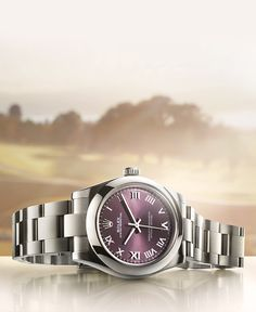 The Rolex Oyster Perpetual is a symbol of universal and classic style. The vibrant red grape dial looks perfectly at home amongst the sculpted greens of the 2016 Evian Championship.