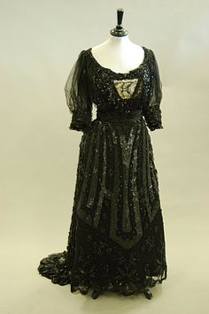 A black sequined ball gown circa 1900, with elaborate trained skirt, colourful silk embroidery to the bodice