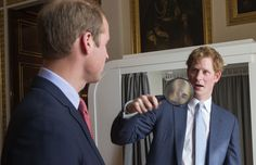 Prince Harry inspects his brother Prince William, Duke of Cambridge with a magnifying glass during the launch of The Queen's Young Leaders Programme at Buckingham Palace on July 9, 2014