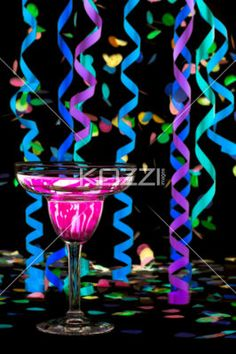 image of pink drink and decorations. - Close-up shot of martini with pink drink and colorful streamers and confetti over dark background.