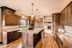 HGTV features an open transitional rustic kitchen with a kitchen island, dark stained wood cabinets, rustic hardwood floors and contemporary pendant lights.