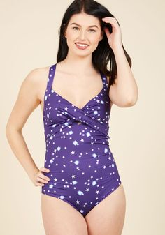 Read Between the Coastlines One-Piece Swimsuit in Universe   Mod Retro Vintage Bathing Suits   ModCloth.com  Some see the shining sun as an invitation to lay out, but in this one-piece bathing suit, your first stop is the waves! When you return to the shore for a snack, this galaxy-printed design from High Dive by ModCloth will catch eyes with its flattering crisscross bust and bow-tied back straps, making 'sand-lubbers' realize a refreshing swim is a righteous idea.