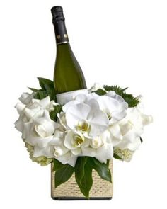 Blooms & Bubbles - Floral ArtA bottle of champagne nestled within a bed of crisp winter white flowers.