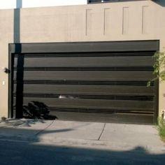 Puerta de garage de herrería con barras gruesas horizontales que dan privacidad y permiten la entrada de luz