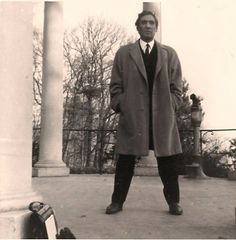 WIESBADEN LANDMARK, DIEGO VOCI: This 1966 photo believed to be at the landmark Greek Chapel (Griecehische Kapelle) atop Neroberg.  The telescope provides a great view of Wiesbaden, Germany.  Diego is posing looking very official, suit, tie and the briefcase propped against a church pillar. The year prior, Helga and Diego signed a 5 year lease on a house and studio in nearby Wiesbaden.