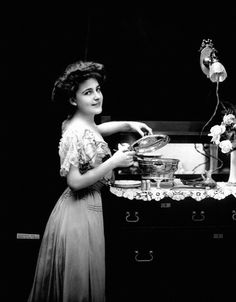 Heating food at a sideboard in an electric serving dish made by General Electric, which is plugged into a light socket, 1908.