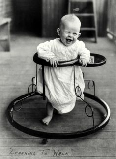 A joyful baby takes a spin in a walker in 1905.