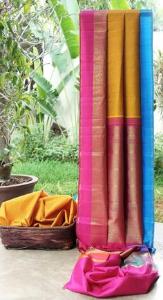 This vibrant sari is a yellow kanchivaram silk with thread brocade all across. One side of the border is in pink and blush pink with gold zari work and the other end is in blue and ocean green with...