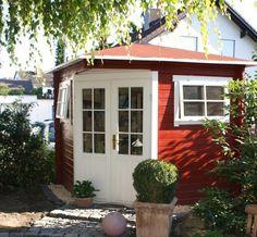 Ein Weg aus Pflastersteinen führt zu diesem 5-Eck-Gartenhaus in Schwedenrot. Die großen Flügeltüren werden durch einen Anstrich in Weiß betont.