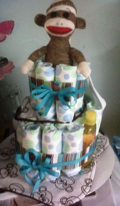 Sock Monkey diaper cake includes diapers, baby wash, socks, bib, burp cloth, and baby powder.