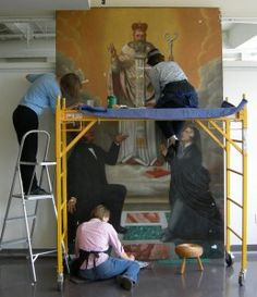 Conservators working to treat a large painting