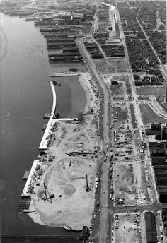 """Photo looking south from above the Benjamin Franklin Bridge shows Penn's Landing redevelopment project amid piers on the Delaware River. Image shows cleared blocks along Delaware Avenue and the Delaware Expressway, or Interstate 95, under construction (top, right of center). """"The long curving line is the 'Embarcadero,' where tourists will embark on ocean voyages.""""  Philadelphia Evening Bulletin, May 5th, 1969"""
