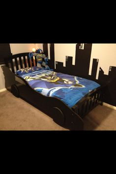 DIY Batmobile car bed Use a jigsaw to cut the Batmobile shape out of ply wood. add some wheels. Paint it black. Screw it to the bed. I also painted buildings silhouette city on the wall and added some batman quilt covers. DONE!