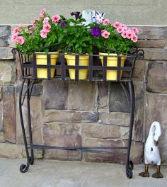 I like this wrought iron plant stand with three clay pots side by side, almost like a sofa table height.  I love the pop of color.  Now I have to look for this stand!