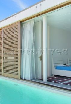 Lapacho wood sliding shutters of bedroom open directly to swimming pool