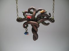 This tree pendant was hand-sculpted out of matte and shimmering polymer clay with hand-painted details. Each section is special, from swirling wood tones, branches curved into a heart, and a baby birdie swooping down from the tree. The pendant measures approximately 2-3/4 inches wide by 2-1/2 inches tall. The details are carried through the rest of the necklace with an antique brass chain, flower connectors, and a leaf drop. The necklace ends in a matching lobster claw clasp and jum...