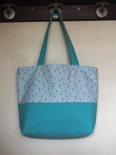 Ce sac en toile de coton bleu turquoise et imprimés triangles est réversible. Il sera parfait pour vous accompagner dans vos séances shopping, vos