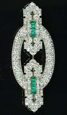 A fine Art Deco emerald and diamond brooch, by Lacloche, circa 1930, the oval plaque with buckle-shaped terminals pavé-set with old brilliant and single-cut diamonds and buff top calibré-cut emerald highlights, signed Lacloche Paris and numbered in two places, partially obscured maker's mark, French assay mark. #ArtDeco #Lacloche #brooch